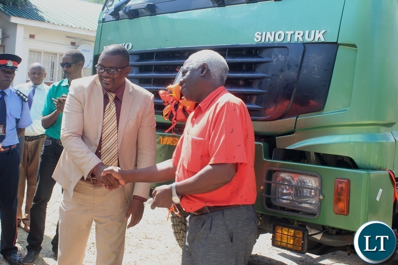 Western Province Deputy Permanent Secretary Bernard Chomba (l) congratulates Mongu Mayor Akayombokwa Kusiyo (r) shortly after handing over a truck to Mongu Municipal Council for garbage collection at a total cost of k784, 200.80 in Mongu, Western Province.
