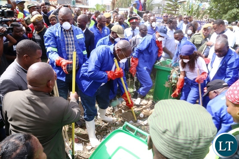 Lusaka Province Minister Bowman Lusambo and Minister of Health Chitalu Chilufya cleaning during the Cavendish University Keep Zambia Clean, Health and Green at Kafue Roundabout