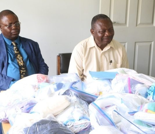 Church of God National overseer Bishop Joseph Ndashe flanked Bishop Michael Siwela with gives Christmas gift to a patient Esther Zulu at Liteta Hospital during the giving of Christmas presents