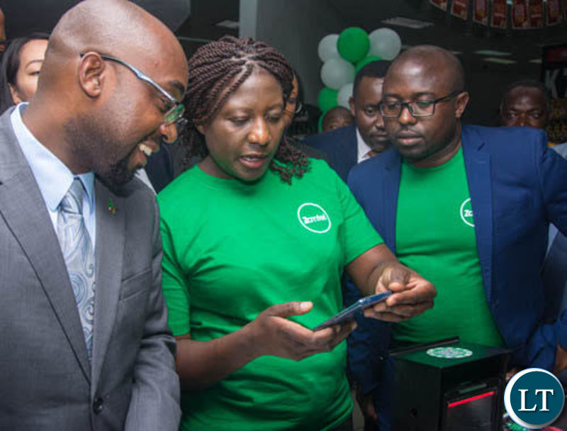Transport and Communications Minister Brian Mushimba and Zamtel Acting Chief Information Officer Jason Mwanza look on as Zamtel Products Manager Mrs. Comfort Nyondo Mbulo demonstrates how ZamPay APP operates at Spar Arcades