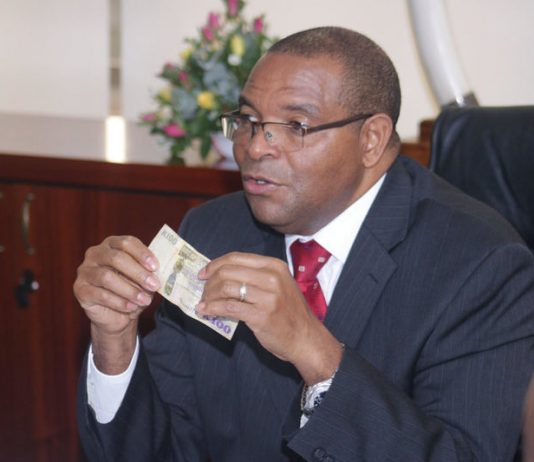 Bank of Zambia Governor Denny Kalyalya displays a Kwacha note to Journalists during a news briefing