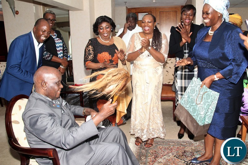 Zambia 1st president Kenneth Kaunda branding a fly chaser given by some Africa high commissioner ladies  accredited to Zambia.