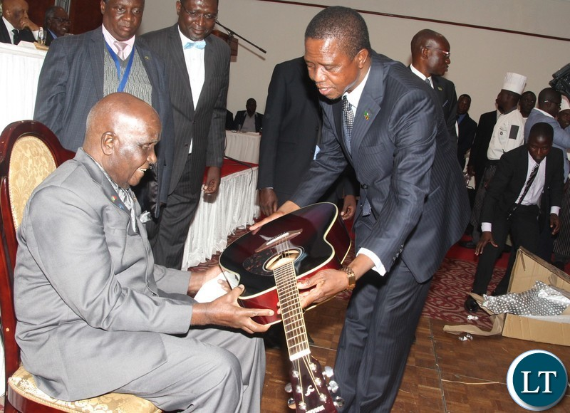 Zambia 1st President Kenneth Kaunda receiving a guitar gift from Zambia President Edgar Chawa Lungu and start to play it thereafter during the celebrations of  the 95th birthday of Kenneth Kaunda at Lusaka Taj Pamodzi Hotel