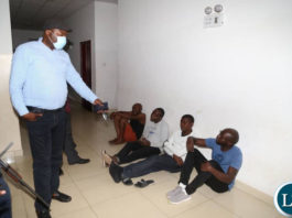 Lusaka Province Minister Bowman Lusambo interrogates some people found drinking beers in bars in Chelstone area on Saturday evening before apprehending them for disobeying coronavirus regulations