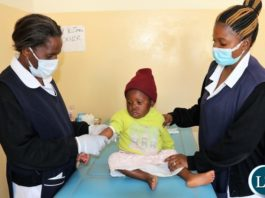 Nurses prepare a child for blood lead level testing