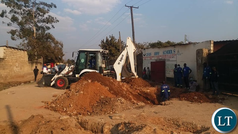 Lusaka Water & Sewerage Company workers  in Mtendere B trying to establish source of water contamination.