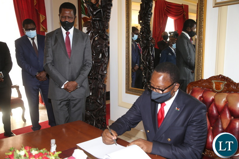 Malawian President Dr.Lazarous Chakwera signs a visitors book after bilateral talks with President Edgar Lungu at State House