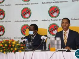 -Electoral Commission of Zambia Chief Electoral Officer Patrick Nshindano flanked by Electoral Commission of Zambia Chairperson Judge Esau Chulu speaking during the launch of online voter registration at Mulungushi International Conference center.