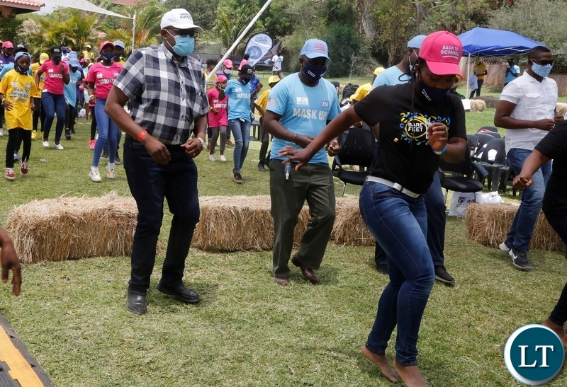 Ministry of Health Permanent Secretary for technical services Dr Kennedy Malama (left)  joins pupils from different schools in dancing during the back to school Coronavirus awareness entertainment programme in Lusaka,s new Kasama