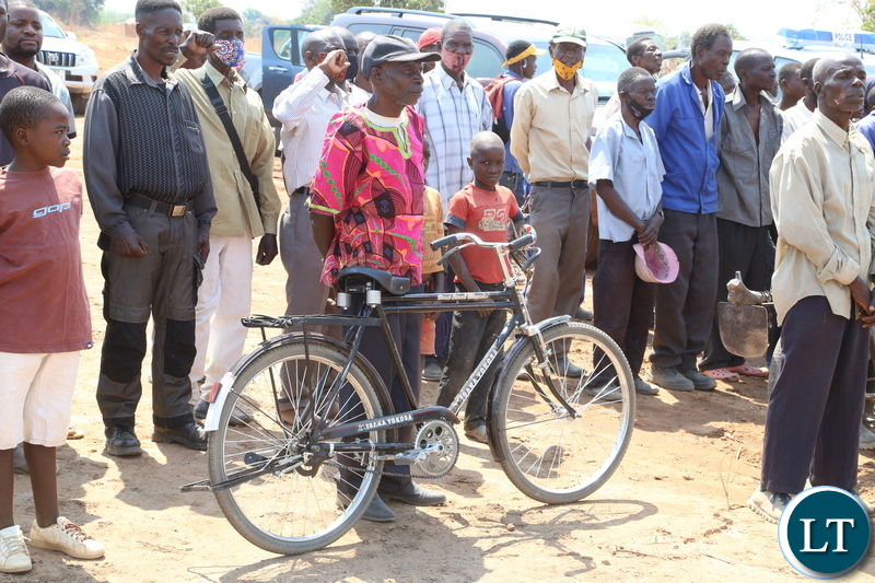 A beneficiary with a bicycle waits to receive the land title from the Vice President Inonge Wina during the handover cement, iron sheets and blocks to the flood and displaced victims in Mufuchani-Kitwe