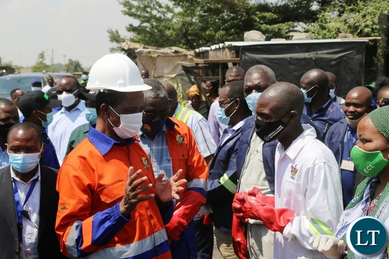 President Edgar Lungu confers with mandevu councillorTeddy Mwaba  during the drainage clean up exercise in Lusaka.