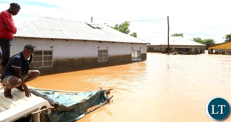 Same Mumbwa residents watch there submerged house hopeless after the Kandesha dam burst it banks causing the flash floods yesterday. Sunday, December 27, 2020. Picture by ROYD SIBAJENE/ZANIS